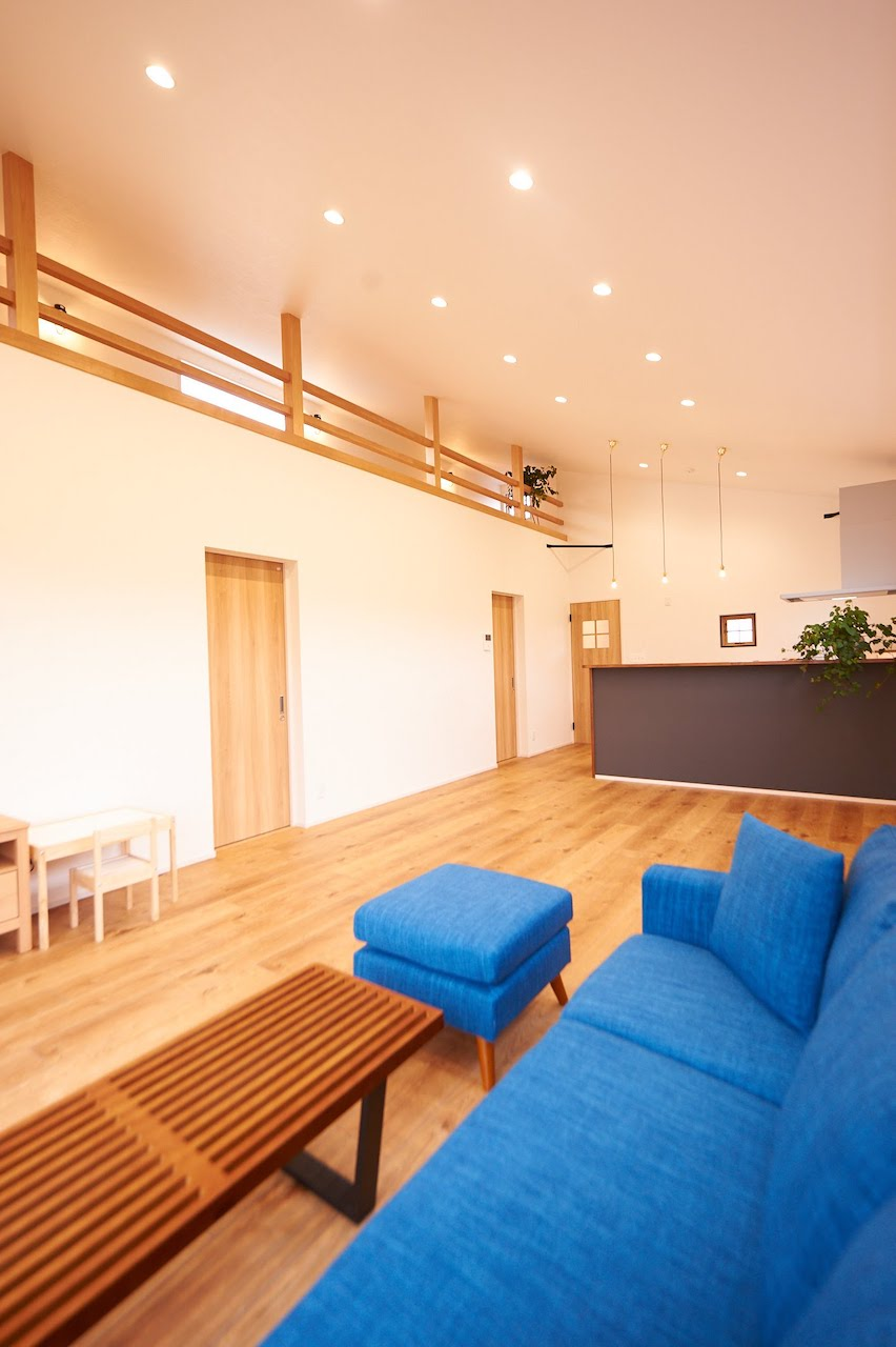 一級建築士事務所GO_AN (ゴアン)【デザイン住宅、建築家、平屋】広々としたリビング。屋根の形状を生かし吹き抜けとロフトを設けた。床はペットの犬に優しい木目調のビニールタイル。キッチンには来客時に玄関とのコミュニケーションが取れる小窓を取り付けた
