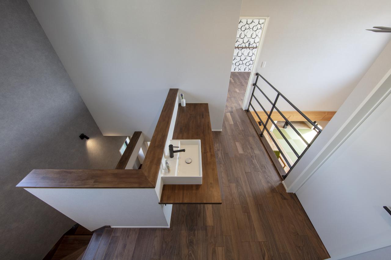 一級建築士事務所GO_AN (ゴアン)【デザイン住宅、間取り、建築家】階段とLDK、ふたつの吹き抜けを渡り廊下で渡っていくようなイメージの2階ホール。それぞれの部屋の中心に洗面を設けた。寝室を設けた2階はダークトーンのフローリングでコーディネートしている。階段側吹き抜けは、暗くなりがちな北側廊下に光を導く意図もある