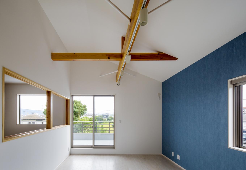 2階LDK。屋根裏空間を利用することで高い天井を取ることができ、また建物中央部にある吹抜け空間とつながる開口部を作ることで、広々とした開放的なLDKを実現。また1階は両親が住むので落ち着いた空間としたが、2階は子ども家族が住むのでカラフルなデザインクロスを使って若者向けの空間とし、上下階でデザインのメリハリをつけた