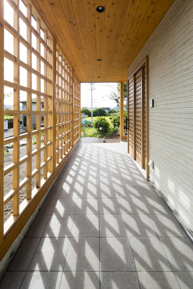 駐車場から玄関につながるアプローチ。屋根もついているので雨の日でも濡れずに移動できる。晴れた日は影も合わせて「格子の空間」に