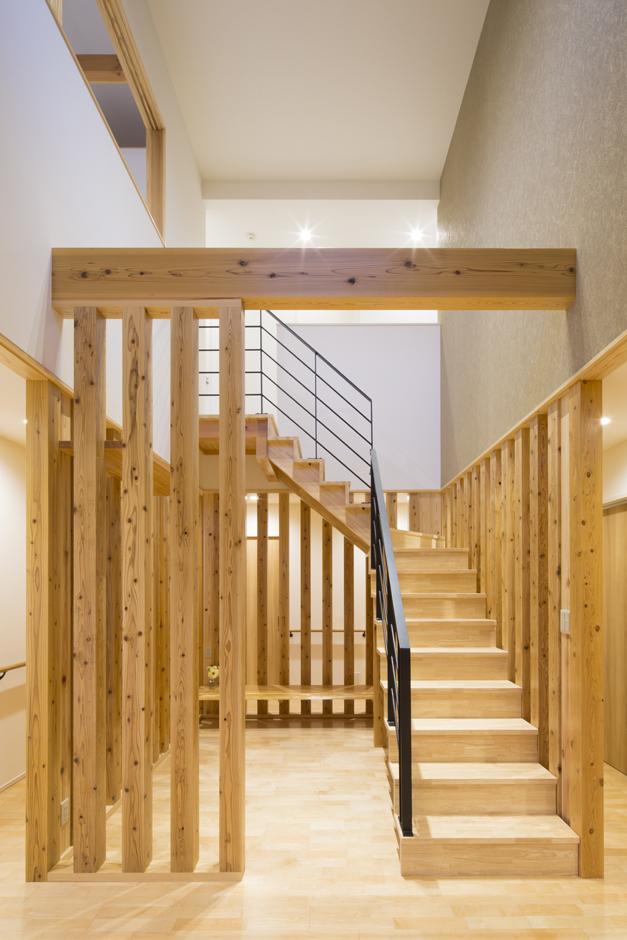 建物中央にある吹抜状の杉柱に囲まれた階段室。杉柱の隙間から奥の空間が見えることで閉鎖感がなくなり、空間全体の一体感が生まれた。1階の床暖房やペレットストーブで暖められた熱を2階のホールやLDKへ伝える役目もしている