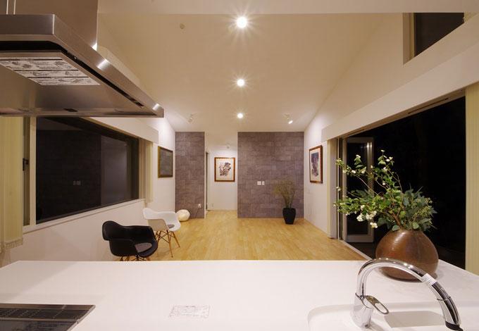 一級建築士事務所GO_AN (ゴアン)【1000万円台、デザイン住宅、ペット】キッチンから見たLDK。2つの大きな窓でLDKを挟むことにより、閉鎖感をなくし、高い勾配天井によって空間に動きを出している。これだけの大空間でも床暖房により、冬でも快適に過ごすことができる