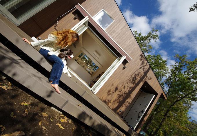 一級建築士事務所GO_AN (ゴアン)【1000万円台、デザイン住宅、ペット】外観。森と一体となるようにグッドデザイン賞を受賞した木目調サイディングを外壁に採用。開閉できるオーニングテントや愛犬用の温水式シャワー水栓も外部に設置。ウッドデッキを階段状に設計することで住宅全体の立体感を作り出した