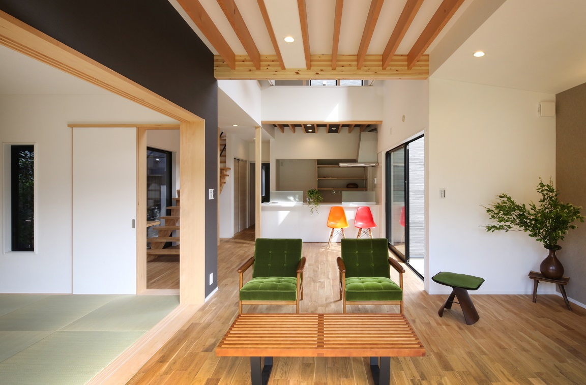 ウッドデッキから見たLDK。天井は張らず、2階床の構造体を表しデザインすることでLDKの広さを演出。隣接する和室も扉の開閉でLDKとつながる