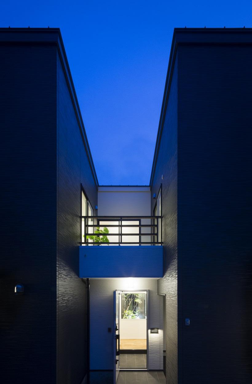 玄関アプローチの夕景。2つの箱に囲まれたスリット状の空間から、内部空間に導かれる。玄関に入っても光庭があるため閉鎖感がない。玄関上部は子どもバルコニーになっている