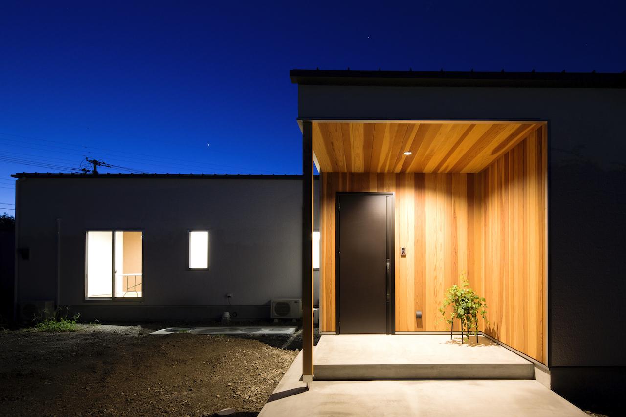 一級建築士事務所GO_AN (ゴアン)【1000万円台、デザイン住宅、平屋】大通りからは見えない位置に設計した、耐候性のあるレッドシダーの無垢材で仕上げた玄関。赤身と白身のムラが美しい。雨に濡れないよう、ポーチを広く取った