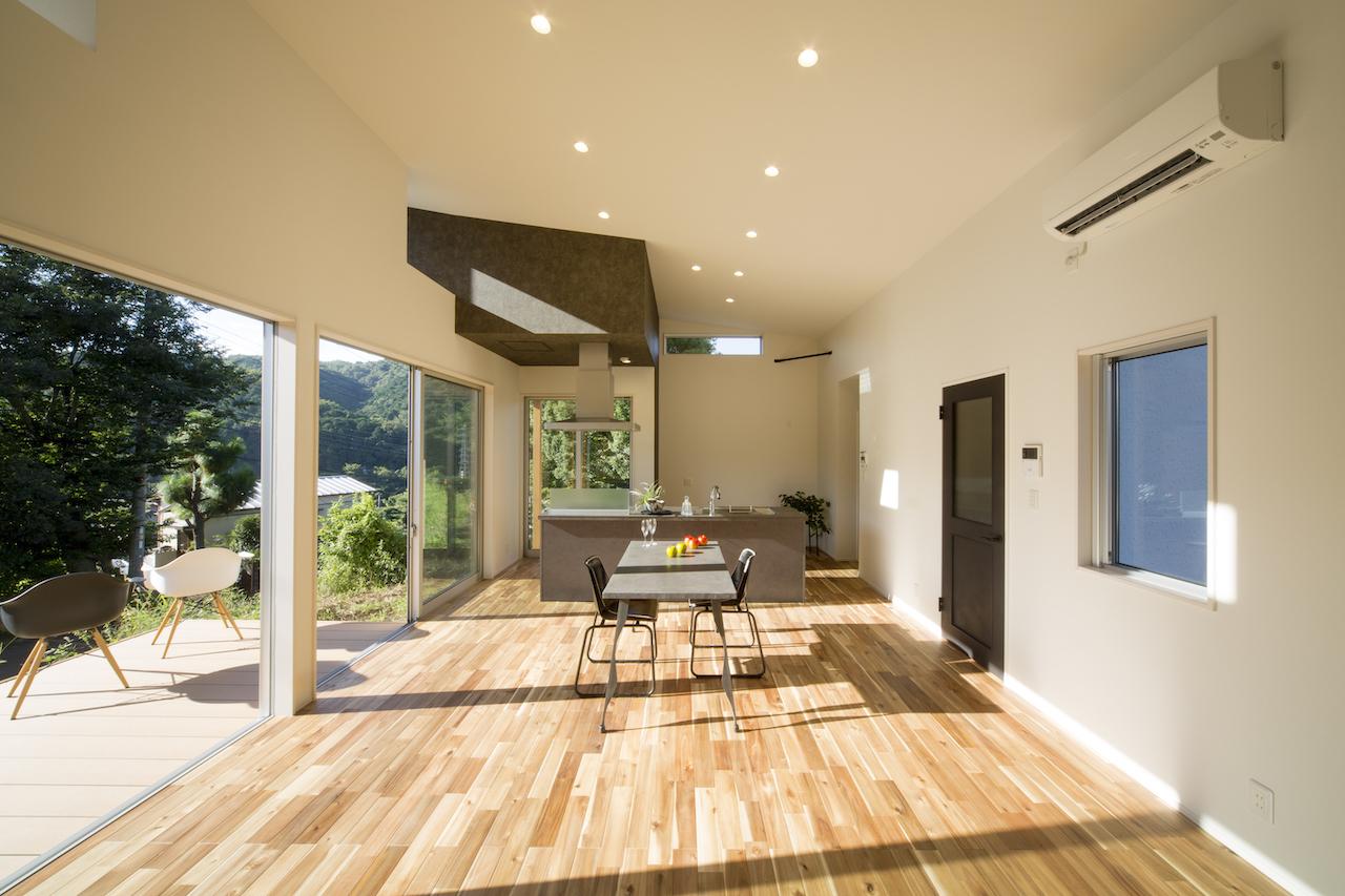 一級建築士事務所GO_AN (ゴアン)【1000万円台、デザイン住宅、平屋】LDKは21畳の広さ。床材は無垢のアカシア、ウッドデッキは人工木材でメンテフリー。平屋だが、屋根裏部分も有効活用し、最大高3.5mの大空間を実現した。換気扇のBOXは造作