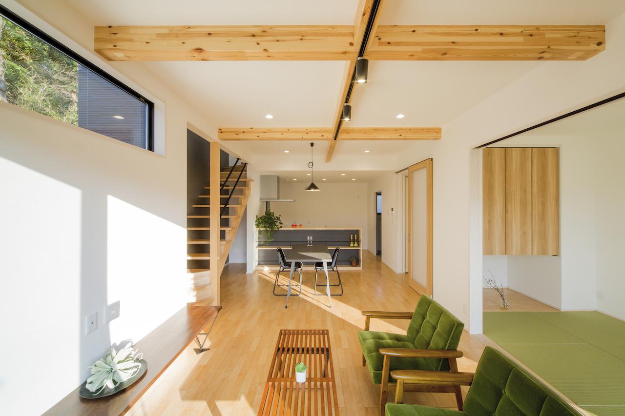 一級建築士事務所GO_AN (ゴアン)【狭小住宅、間取り、建築家】地中熱利用の床暖房システム「SRC基礎」採用で、冬でも暖かなLDK。米松の集成材がアクセントのリビング部は、最大2.7mの高天井。外観と合わせ、ナチュラルな木の色、アイアンの黒、クロスの白で配色した。ハイサイドライトは借景と採光を叶えている