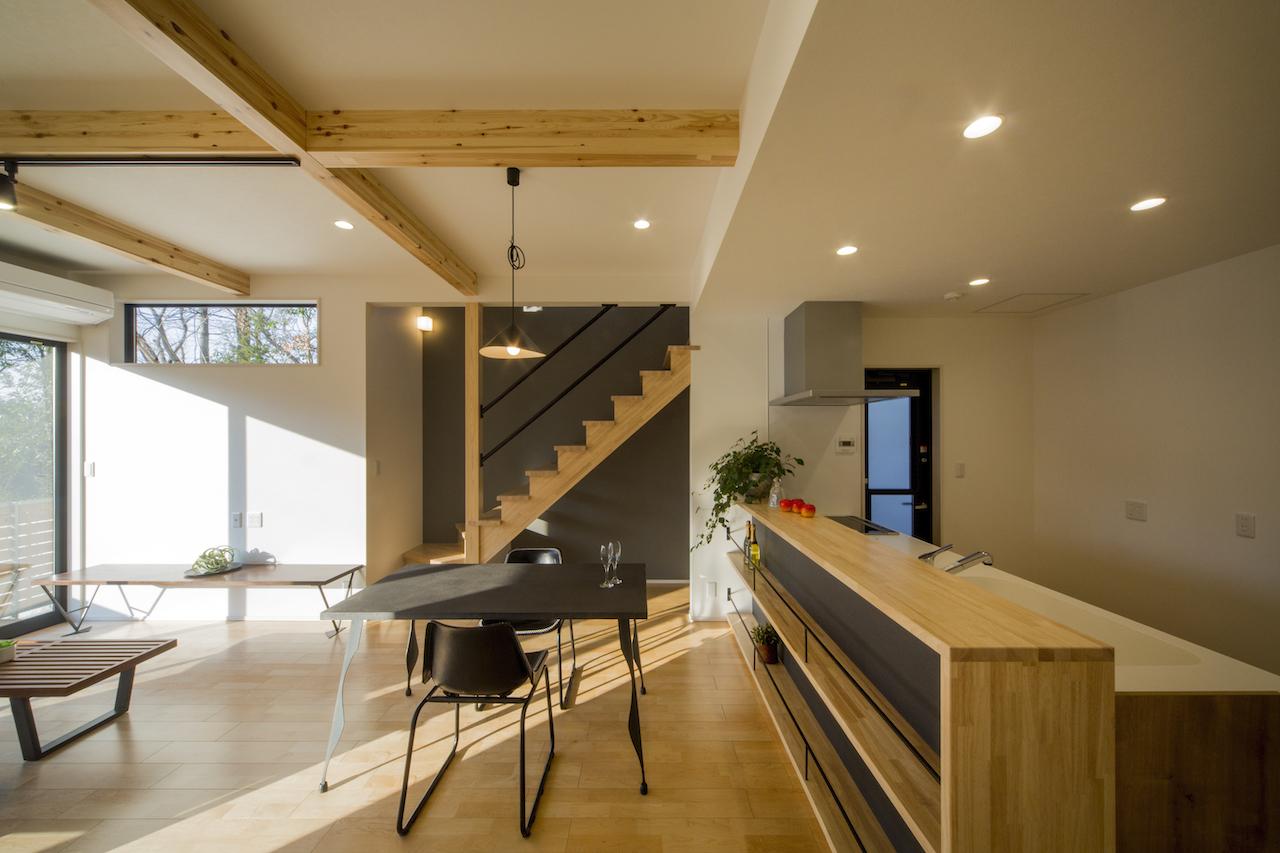 一級建築士事務所GO_AN (ゴアン)【狭小住宅、間取り、建築家】造作のキッチンカウンター。お酒を飲むのが好きなおふたりは、将来前面にお酒を収納するのが楽しみだそう。2階へつながるLDK階段は、下を収納スペースとしても活用可能