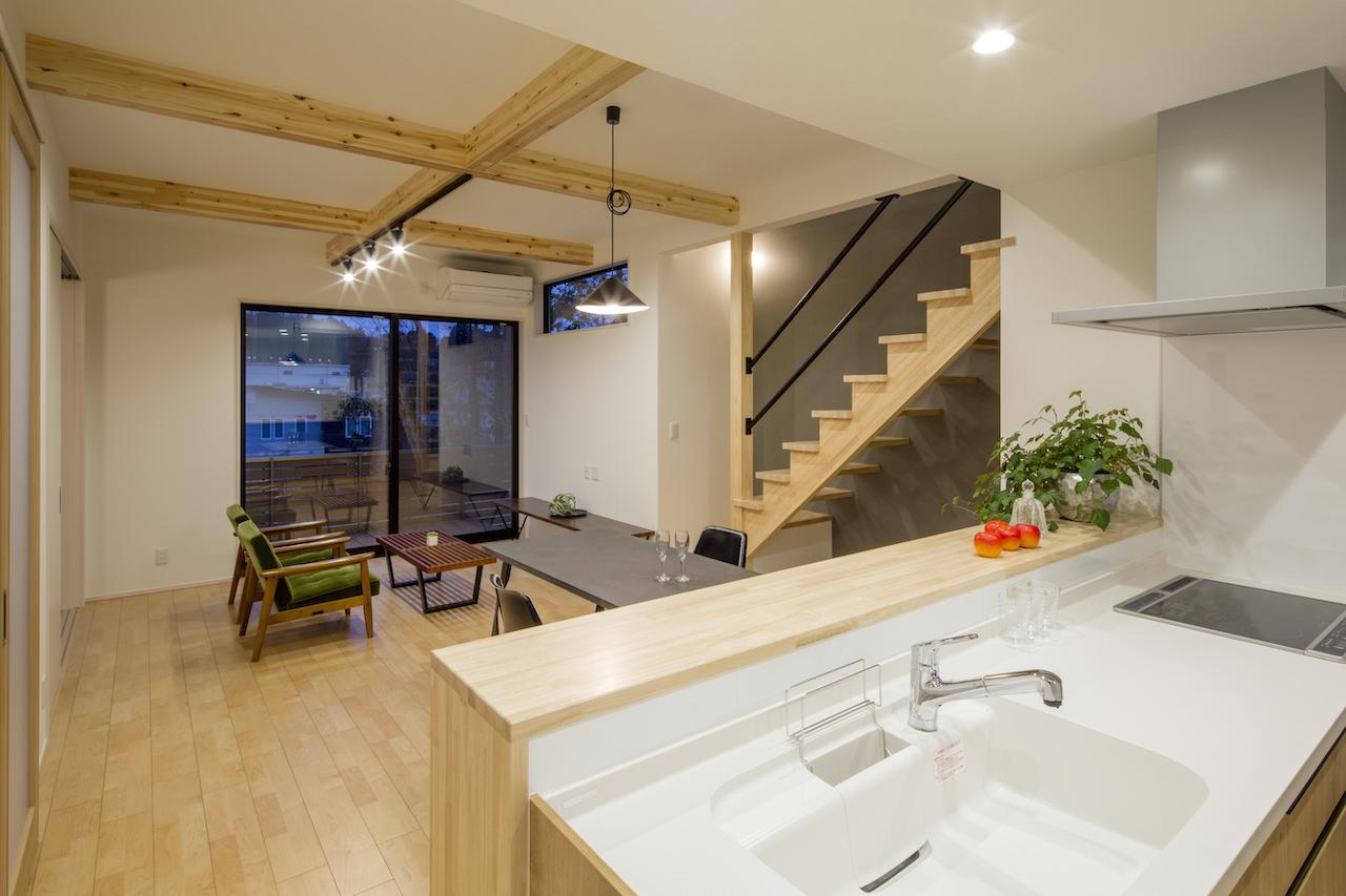 一級建築士事務所GO_AN (ゴアン)【狭小住宅、間取り、建築家】キッチンからリビングを望む。ウッドデッキまで視線が抜け、開放感抜群