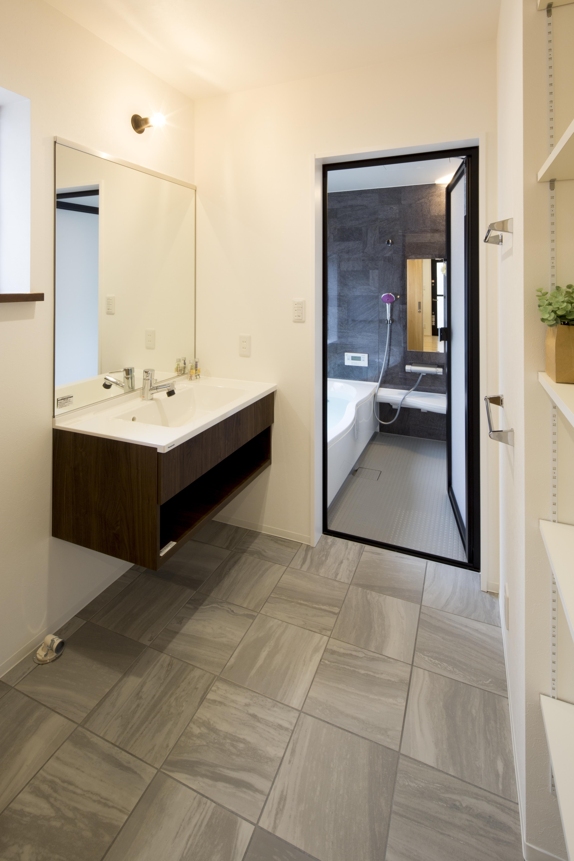 一級建築士事務所GO_AN (ゴアン)【狭小住宅、間取り、建築家】グレーがテーマカラーの洗面床はタイル貼りに。フロートタイプの洗面は掃除も楽々。あえて一枚鏡を採用することでスタイリッシュに仕上げている