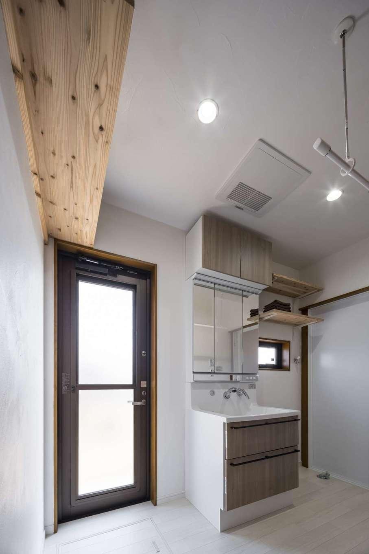 WOODLIFE style 丸守木材【自然素材、間取り、平屋】洗面脱衣室は室内干しスペースも兼ねている。勝手口の頭上にある木の収納棚は大工が造作したもの。