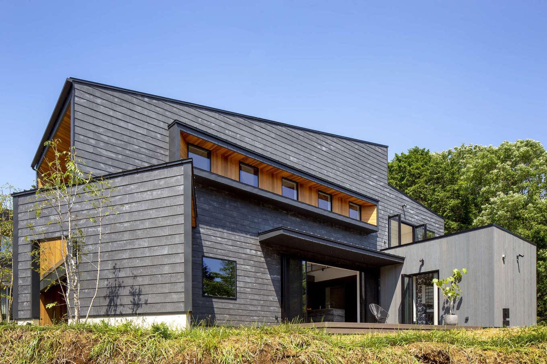 一級建築士事務所GO_AN (ゴアン)【駿東郡長泉町・オープンハウス】自然豊かなロケーションに佇むオープンハウス。「ザ・建築家の家」と呼ぶにふさわしい独創的なプロポーションに思わずため息が漏れる。セメント素材の風合いが美しい外壁は、スターバックス浜松城公園店と同じSOLID(ソリド)で、職人が一枚一枚手作業で貼った