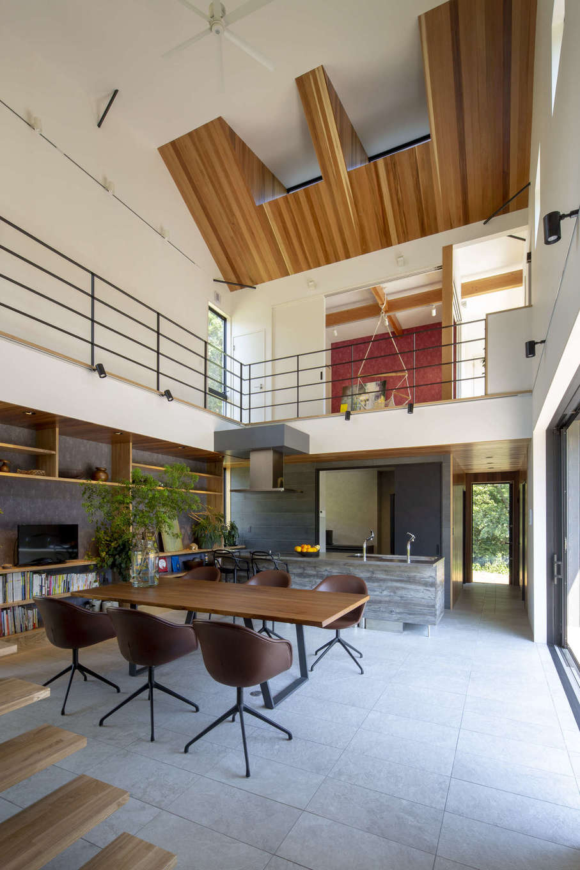 一級建築士事務所GO_AN (ゴアン)【駿東郡長泉町・オープンハウス】リゾートのような開放感に満ちた、ダイナミックな吹抜けのLDK。木、タイル、アイアン、クロスといった異素材がバランスよく調和し、心落ち着く空間に。これほど大きな吹抜けがあっても、地中熱を利用したSRC基礎により、家全体が温度差のない快適な住空間となる