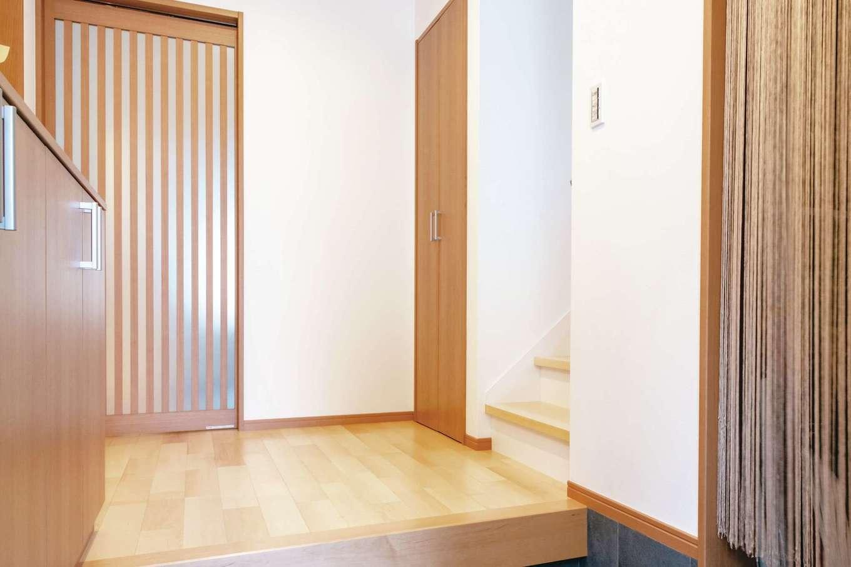 ハウジング小林【デザイン住宅、二世帯住宅、間取り】シューズクローク付きの玄関。階段を上がると子世帯のスペース。格子戸の奥は共有のLDKスペース