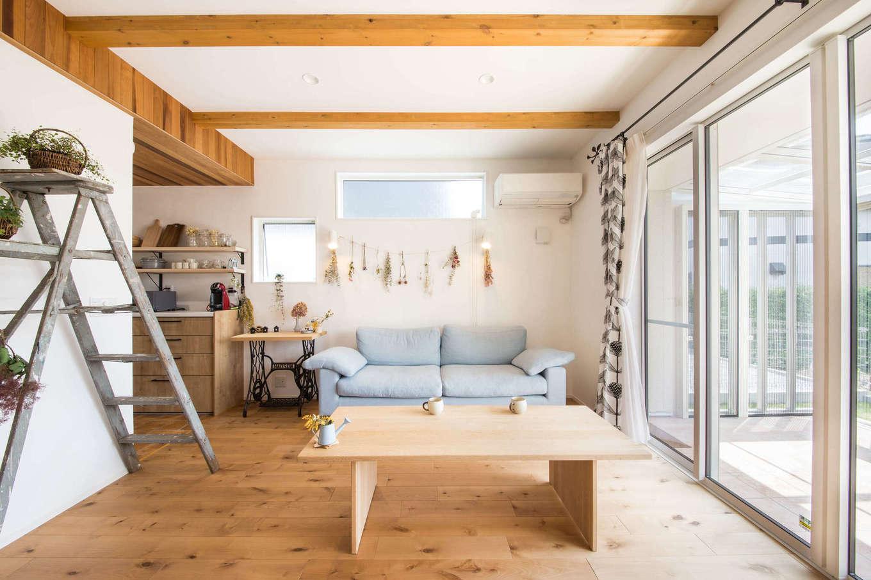 子育て安心住宅&デザインラボ【デザイン住宅、平屋、インテリア】木の温もりにあふれた空間に、シャビーシックなインテリアがマッチしたリビング。等間隔に並んだ化粧梁が空間の広がりを強調している。大きな窓から柔らかな光が降り注ぎ、明るさが室内の奥まで行き渡る