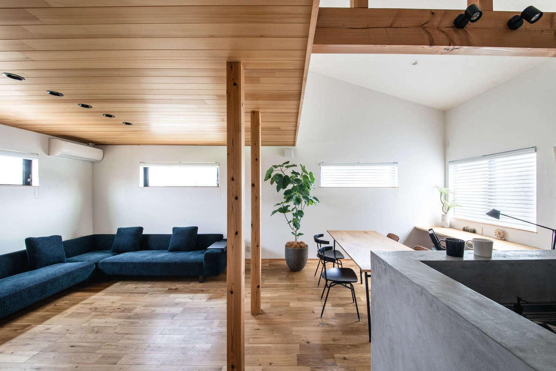 ツリーズ【デザイン住宅、自然素材、間取り】リビングの天井をアガチスの板張りにしてゾーン分け。対面式キッチンは、モールテックスで囲って手元を隠すことですっきりとした印象に
