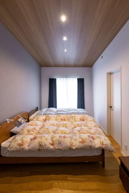 ユートピア建設【収納力、省エネ、間取り】勾配天井が目を引く寝室は、グレーのアクセント壁で落ち着いた雰囲気に仕上げた