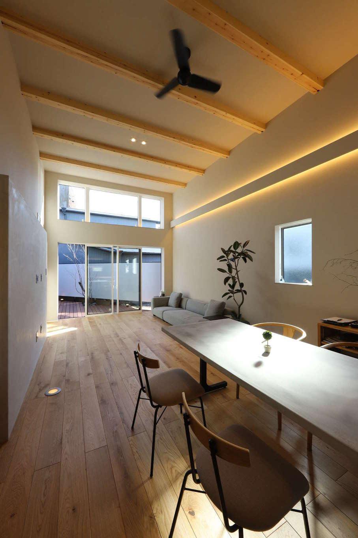 KOZEN-STYLE コバヤシホーム【デザイン住宅、狭小住宅、インテリア】天井高4メートルの吹き抜けのLDKは圧倒的な開放感。テラスに面した大開口が広がりをいっそう強調し、20畳という実寸よりも遥かに広く感じられる。内装は、無垢の床が引き立つシンプル&ナチュラルなデザイン。リアテック・コンクリートを壁に採用し、無機質で洗練されたイメージをプラス