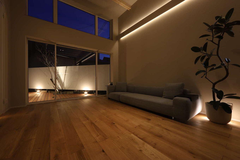 KOZEN-STYLE コバヤシホーム【デザイン住宅、狭小住宅、インテリア】間接照明に照らされて、無垢の床の表情が温かみを感じさせるリビング。テラス側のハイサイドライトから夜空が眺められる