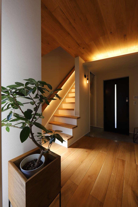 KOZEN-STYLE コバヤシホーム【デザイン住宅、狭小住宅、インテリア】2階に至る階段には、手すりに間接照明が仕込んである。夜の玄関ホールの意匠性が高まるだけでなく、夜間に足元がよく見えるので、階段の上り下りが安全にできる