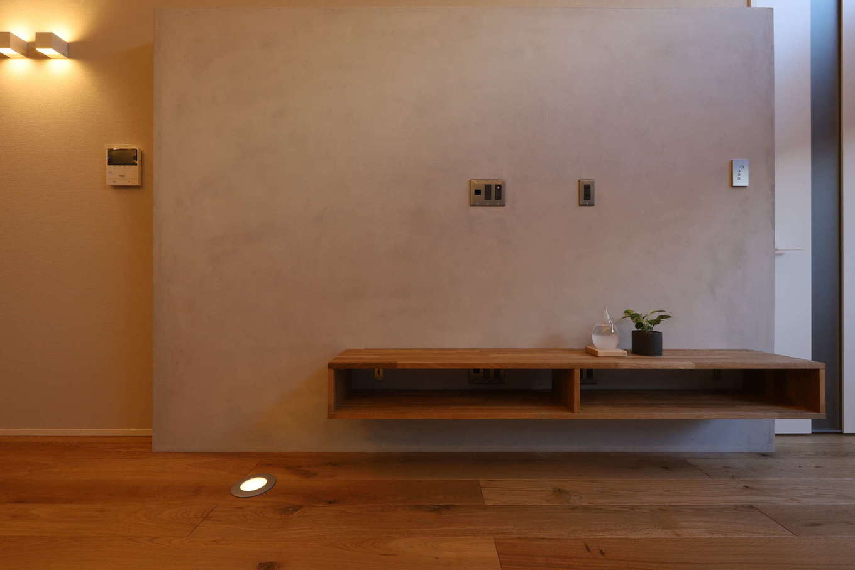 KOZEN-STYLE コバヤシホーム【デザイン住宅、狭小住宅、インテリア】リビングのリアテック・コンクリートの壁に、造作のT Vボードのシンプルなフォルムが映える