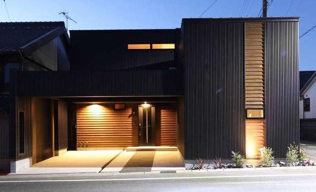 KOZEN-STYLE コバヤシホーム【デザイン住宅、狭小住宅、インテリア】建物は敷地の形状に合わせてテトリス型にデザイン。道路からはシンプルなL字型に見える。ブラックの外壁に木目調を組み合わせたスタイリッシュな外観が照明によく映える