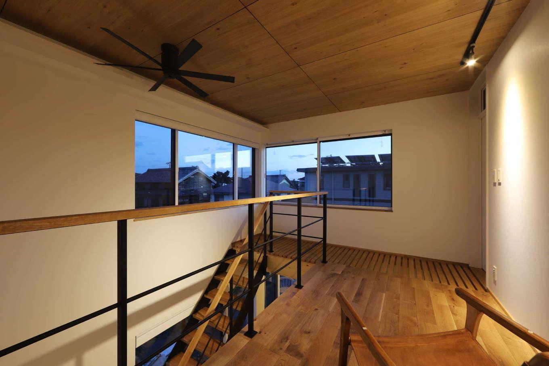 KOZEN-STYLE コバヤシホーム【デザイン住宅、間取り、インテリア】階段を上がると、フリースペースがある。手前の廊下は格子状にして、2階の窓からの光が階下に落ちるように設計されている。パーソナルチェアに腰掛けて、L字型の窓から街の夜景を眺めながらのんびり過ごすのがご主人のお気に入り