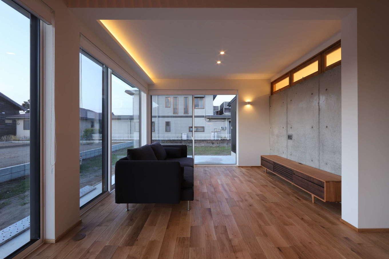 KOZEN-STYLE コバヤシホーム【デザイン住宅、間取り、インテリア】SE構法により、開口部を広く確保したリビング。無垢の床が温かみを感じさせ、シンプルな空間に造作のTVボードが調和している。TVボード側の壁には打ちっぱなしのコンクリートを採用。コンクリートには蓄熱性があるので、室内を暖かく保てる。コンクリート壁の裏側には洗面・脱衣スペースがある