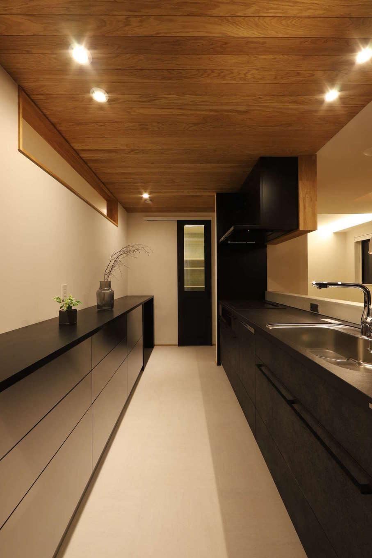 KOZEN-STYLE コバヤシホーム【デザイン住宅、間取り、インテリア】回遊できて動線が便利なアイランドキッチン。正面奥のドアの先にはパントリーがあり、玄関のシューズクロークに繋がっているので、買い物帰りの動線が便利。キッチンの背面にはカウンタータイプの収納スペースを設置。ステンレス扉の「IKEA」製の収納を『コバヤシホーム』のデザイン力でクールにアレンジ
