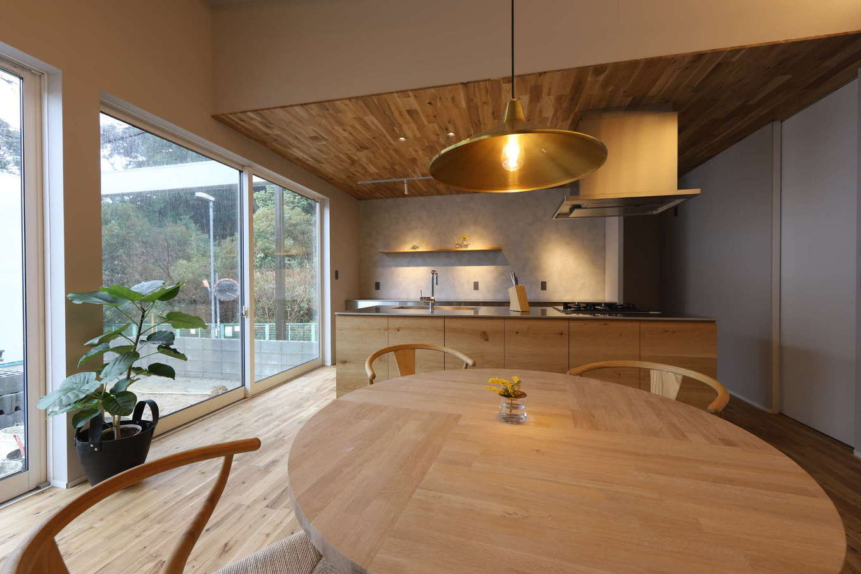 KOZEN-STYLE コバヤシホーム【デザイン住宅、間取り、平屋】キッチンスペースは板張りの下げ天井にしてゾーニング。ワンフロアに共存するキッチン、ダイニング、リビングをこうしてさりげなく区分けすることで、それぞれのスペースに落ち着きが生まれた。開口部とは反対側の壁の奥がベッドルームとなっている