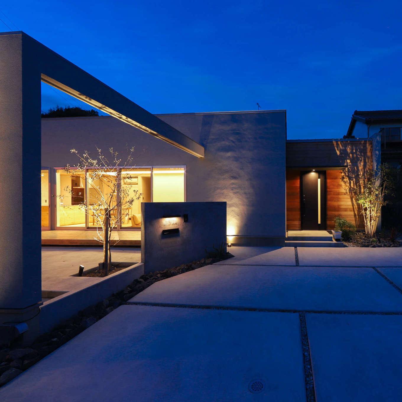 KOZEN-STYLE コバヤシホーム【デザイン住宅、間取り、平屋】建物と庭を一体化した斬新なフォルムが際立つ夜の外観。モルタルの外壁を照明が美しく照らす