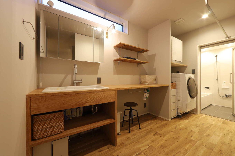 KOZEN-STYLE コバヤシホーム【デザイン住宅、間取り、平屋】洗面&ランドリースペース。造作の洗面台と家事カウンターを並べて設置。室内干しもできるようになっていて、洗濯物を洗って、干して、アイロンがけをして、たたむ作業を1か所で完結できる。ファミリークローゼットがすぐ隣にあるので、しまうのも便利
