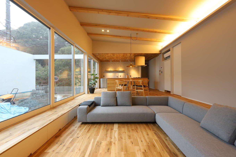 KOZEN-STYLE コバヤシホーム【デザイン住宅、間取り、平屋】リビングは床をステップダウンしてダイニングとゾーニング。スペースに「こもり感」が生まれ、庭を眺める視線も低くなり、落ち着いてくつろげる。窓際には収納付きのベンチを設置