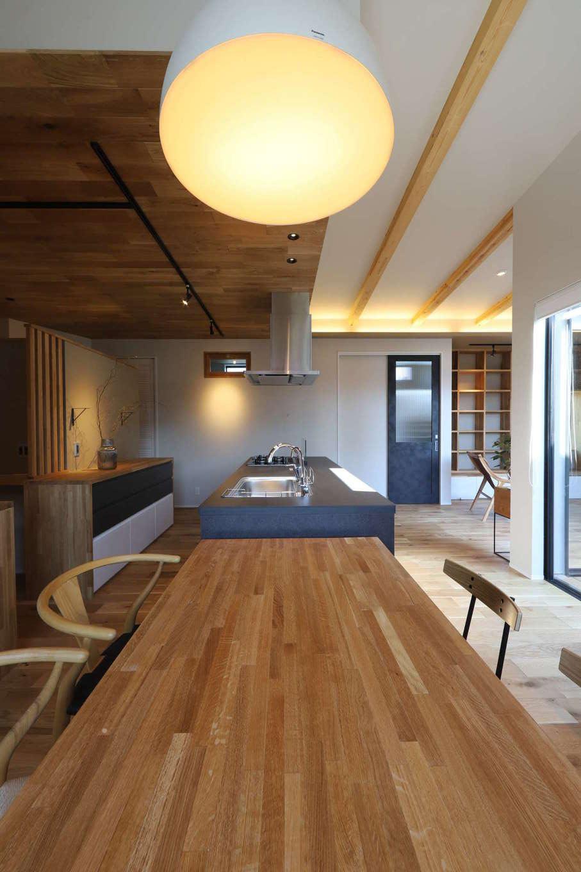 KOZEN-STYLE コバヤシホーム【デザイン住宅、間取り、インテリア】キッチンスペースの天井を板張りにしてゾーニング。アイランドキッチンとダイニングテーブルを並べて配置し、回遊できる動線を確保。配膳や片付けがラクにできる