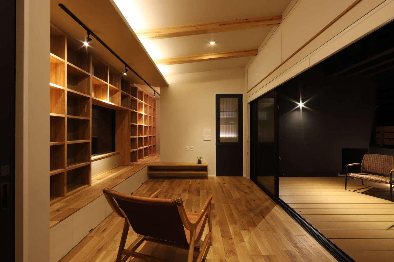 KOZEN-STYLE コバヤシホーム【デザイン住宅、間取り、インテリア】読書が大好きなご主人のために、リビングの壁一面に書棚スペースを確保。夜は間接照明の灯りに包まれて、心がほどける時間を満喫。読書の途中にアウターリビングに出て気分転換する楽しみも