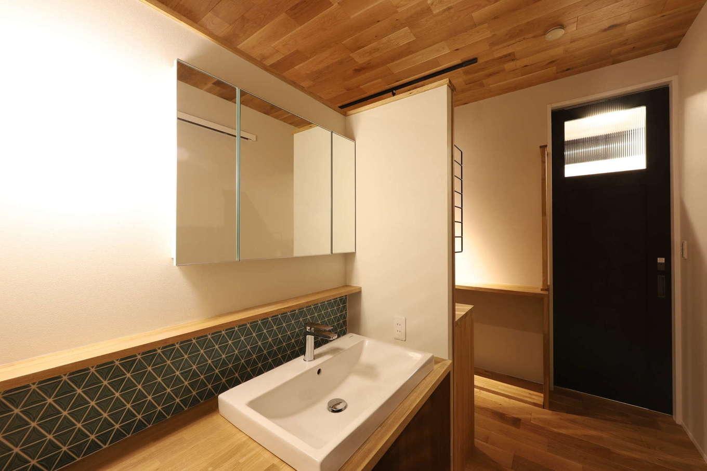KOZEN-STYLE コバヤシホーム【デザイン住宅、間取り、インテリア】板張りの天井とタイル張りの壁がアクセントとなって造作の洗面スペースを引き立てる。洗面台の壁の反対側はキッチンの収納スペース。ドアの奥にはトイレがあり、水回りを集約したことで、家事や生活の動線を短縮化した