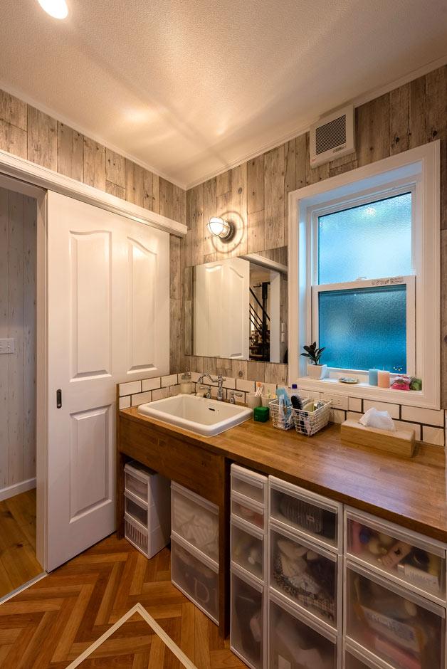 ブルースホーム伊豆 (吉村工務店)【デザイン住宅、輸入住宅、ガレージ】インダストリアルデザインの照明と白いタイルが素敵な手造りの木製洗面台。床はヘリンボーンで仕上げた