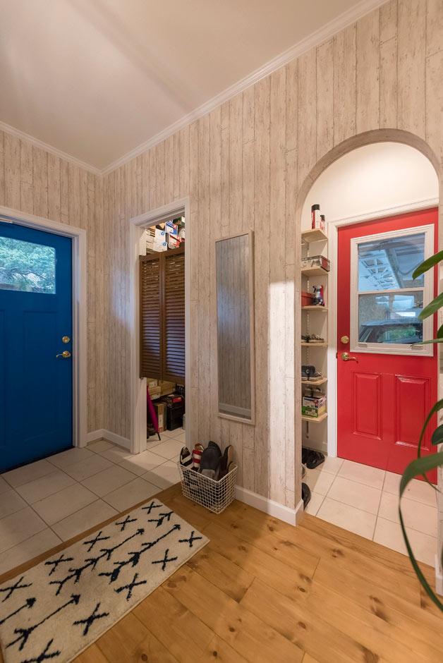 ブルースホーム伊豆 (吉村工務店)【デザイン住宅、輸入住宅、ガレージ】カバードポーチとガレージにつながる玄関。アメリカンポップなブルーとレッドの色違いのドアがかっこいい