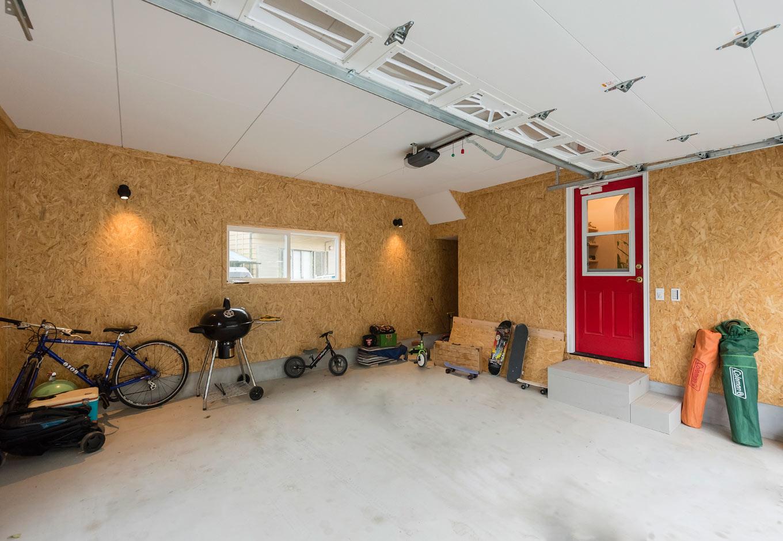 ブルースホーム伊豆 (吉村工務店)【デザイン住宅、輸入住宅、ガレージ】憧れのインナーガレージ。中に車を2台停められ、アウトドアのさまざまな道具や自転車も収納している
