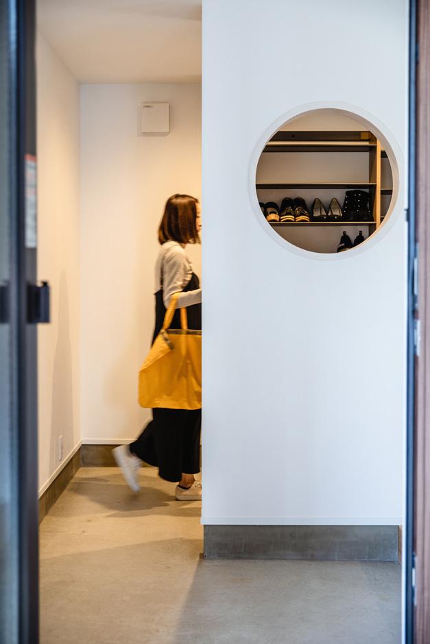 ハウスコネクト【デザイン住宅、収納力、間取り】土間のある玄関ホール。靴が好きな奥さまのために、シューズクローゼットを広めにつくった。丸い穴を開けて遊び心を演出