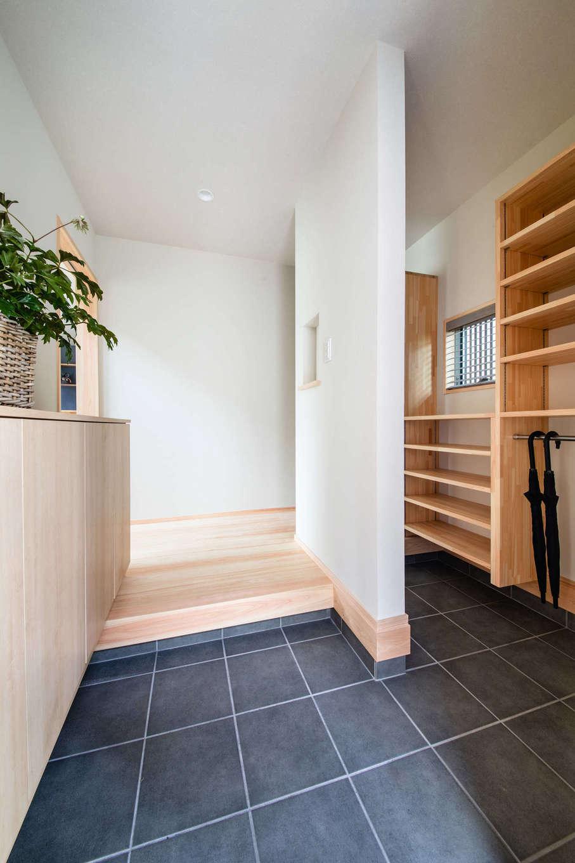 フジモクの家(富士木材)【富士市五貫島667-8・モデルハウス】すっきりとした玄関。右手は家族用の玄関で、高さ可変の棚、傘置き場、上着やコートが掛けられるハンガーパイプなどが用意されている。完全に区切らないことで、広さと明るさがもたらされ、帰宅や訪問の気分を軽くする