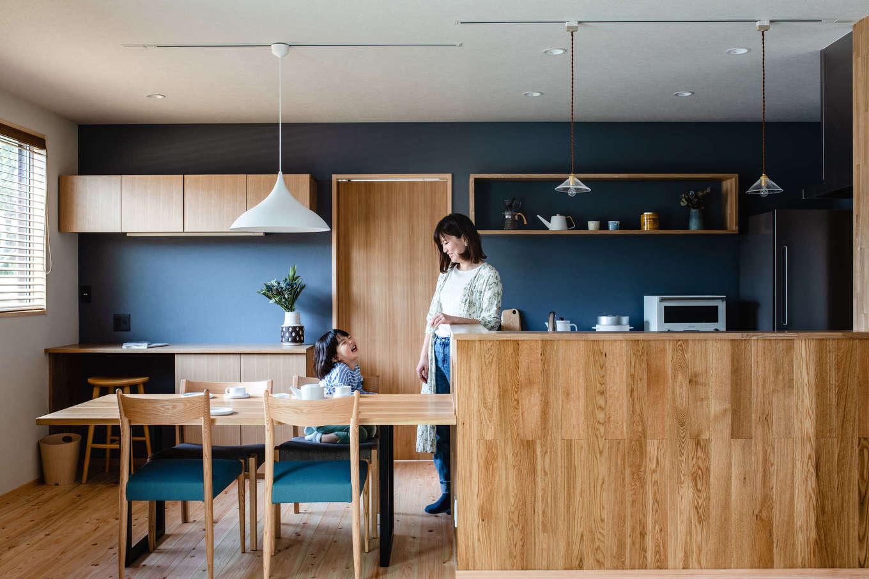 フジモクの家(富士木材)【富士市五貫島667-8・モデルハウス】キッチンの壁には塗り壁のような表情と機能をあわせもつエコフリースを採用。造作仕立ての収納やデスクとの相性もいい。ダイニングやリビングの家具は、人気の家具ブランド「MANUALgraph」とのコラボによる同社オリジナル