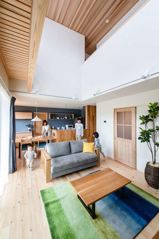 フジモクの家(富士木材)【富士市五貫島667-8・モデルハウス】富士ヒノキが気持ちよく敷き詰められたLDK。ナチュラルな風合いと清々しい香りが家族を包み、踏み心地もやさしい。大きな吹き抜けからはたっぷりの光。天井のレッドシダーが伸びやかな空間にほどよい落ち着きを添えている