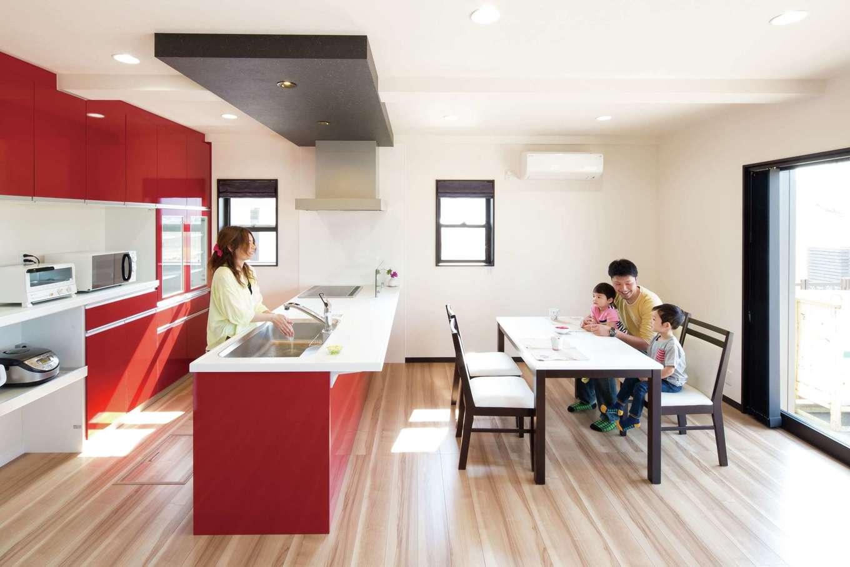 オバタ工務店|南向きの大窓から光が射し込むLDKは、白い壁と赤いキッチンのコントラストがモダン。キッチン上部の折下げ天井が空間にメリハリを加えている