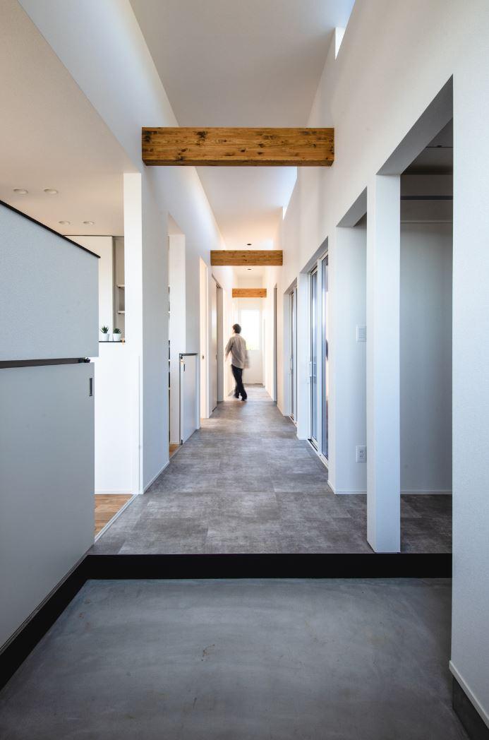 S.CONNECT(エスコネクト)【ペット、建築家、平屋】特にお気に入りという、玄関から部屋の奥までまっすぐ続く広い廊下。コンクリート調のフロアタイルで仕上げてあり、犬がドッグランのように走り回って遊べる。室内の奥行き感も強調されて、いっそう開放的で広々とした印象を与える