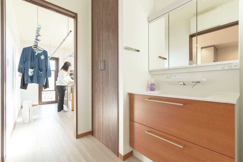 ハウジング小林【デザイン住宅、輸入住宅、間取り】キッチン隣に浴室、洗面、ランドリールームを設計。夜タイマーでセットした洗濯物を朝室内に干し、取り込んだら同じ室内の収納へ。ドアを開けるとウッドデッキにつながる