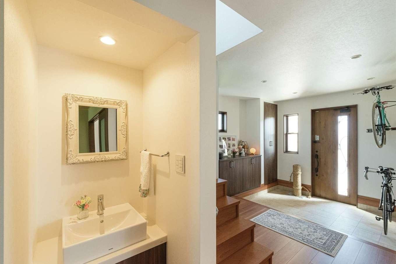 ハウジング小林【デザイン住宅、輸入住宅、間取り】夫妻の自転車をディスプレイできる玄関は、土間部分でメンテナンスができるほど広々。階段脇には手洗い専用の洗面台を造作した