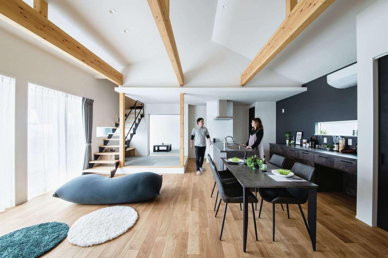 ワンズホーム【デザイン住宅、間取り、建築家】屋根勾配の形を取り入れた天井と、大きな梁の存在感は圧倒的。大窓から差し込む光がオープンキッチンを照らし、黒い壁やドアがアクセントとなる。そして肌触りのいいヨーロピアンオークの床。そのすべてがコラボレートしながら、開放的で暮らしやすい空間が形になった。窓を開け放てばウッドデッキや庭への出入りは自由になり、夫妻の仲間が集ってワイワイ楽しむ風景が目に浮かぶ。高い気密・断熱性で一年中快適に過ごせる