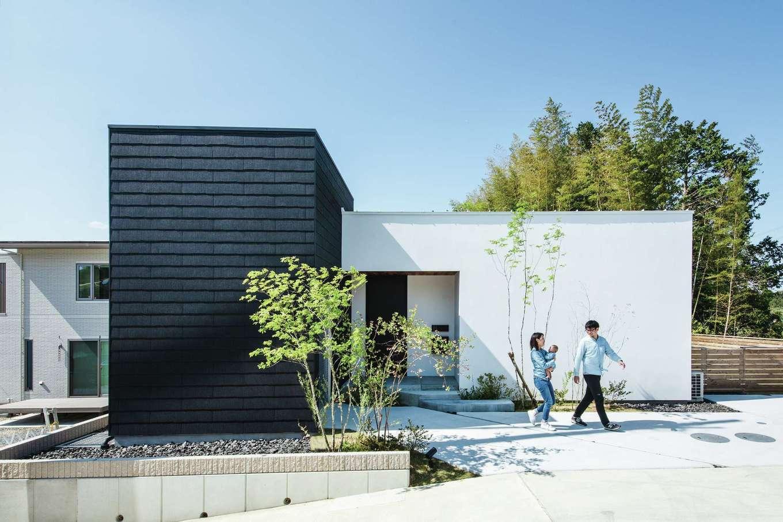 インフィルプラス【デザイン住宅、平屋、ガレージ】緑ゆたかな高台に建つI邸。建物は「コ」の字型の平屋建て。家全体が同社のモデルハウス「HILLA-house」をベースにデザインされている。黒い外壁の部分にご主人のバイクガレージがある